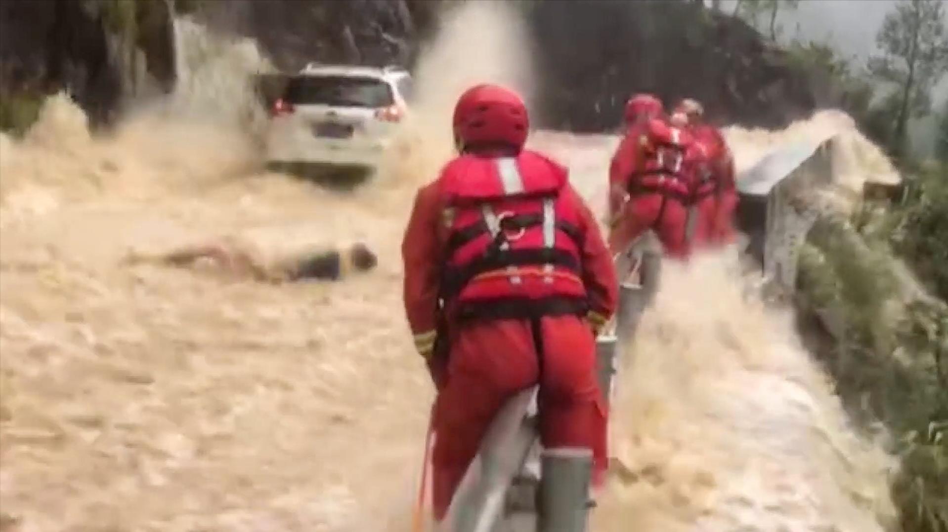 山洪救援现场游客摔倒瞬间被洪水冲走 消防员悬崖边一把将其抓住